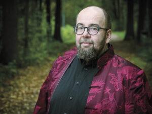 Kuvassa kirjailija J. Pekka Mäkelä metsässä, hänellä on päällään punainen kiinalaistyyppinen takki, jossa lohikäärmeitä.