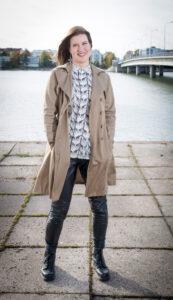 Kirjailija Elina Rouhiaisen kuva, taustalla silta ja kaupunkimaisemaa.