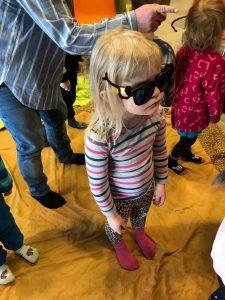 Ett barn klädd i randiga kläder och svarta solglassögon.