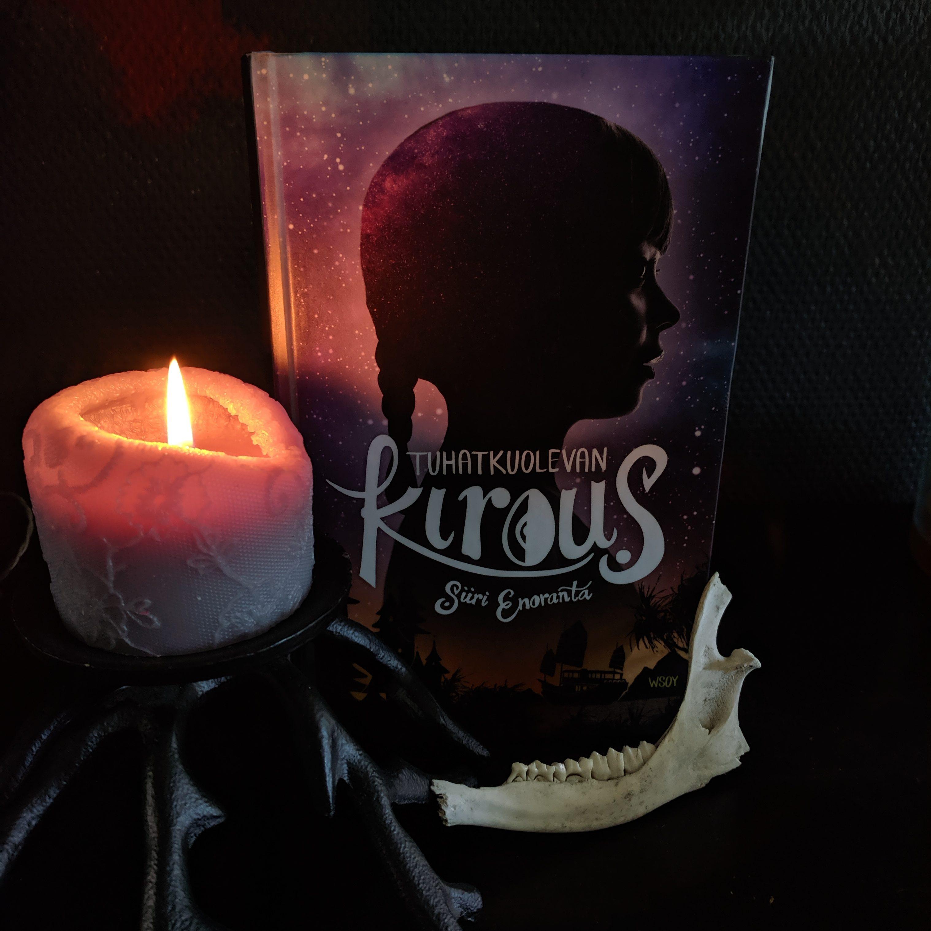 Kynttilä palaa kirjan Tuhatkuolevan kirous -vierellä