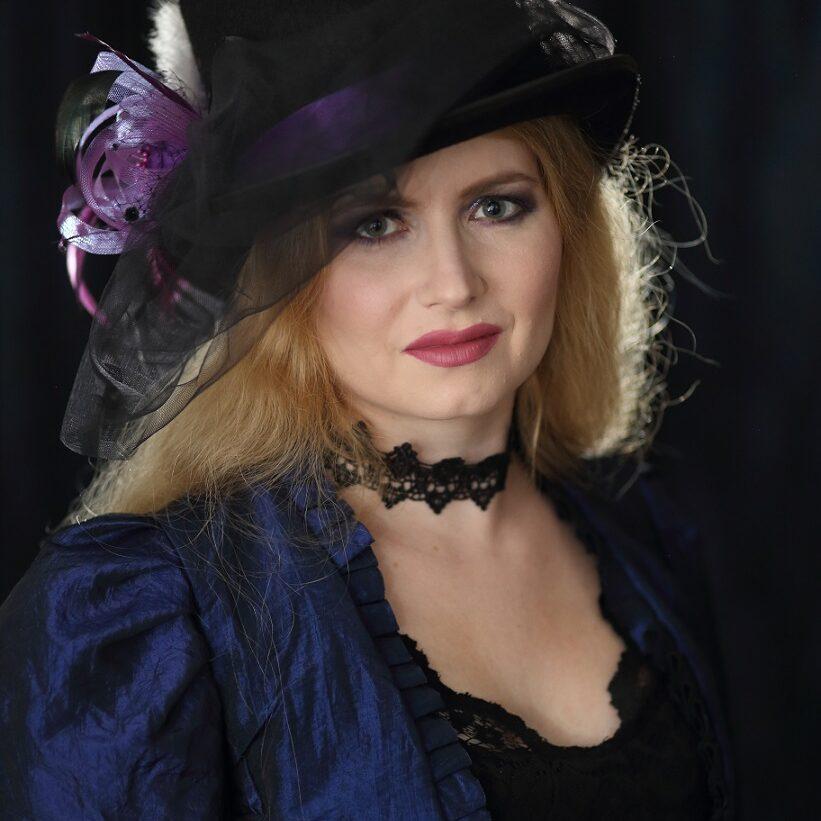 Kirjailija Sini Helminen sinisessä puvussa ja mustassa hatussa, jossa on violetti nauha.