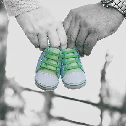 B & W photo. A woman and a man holding a toddler size green sneaker in hands.