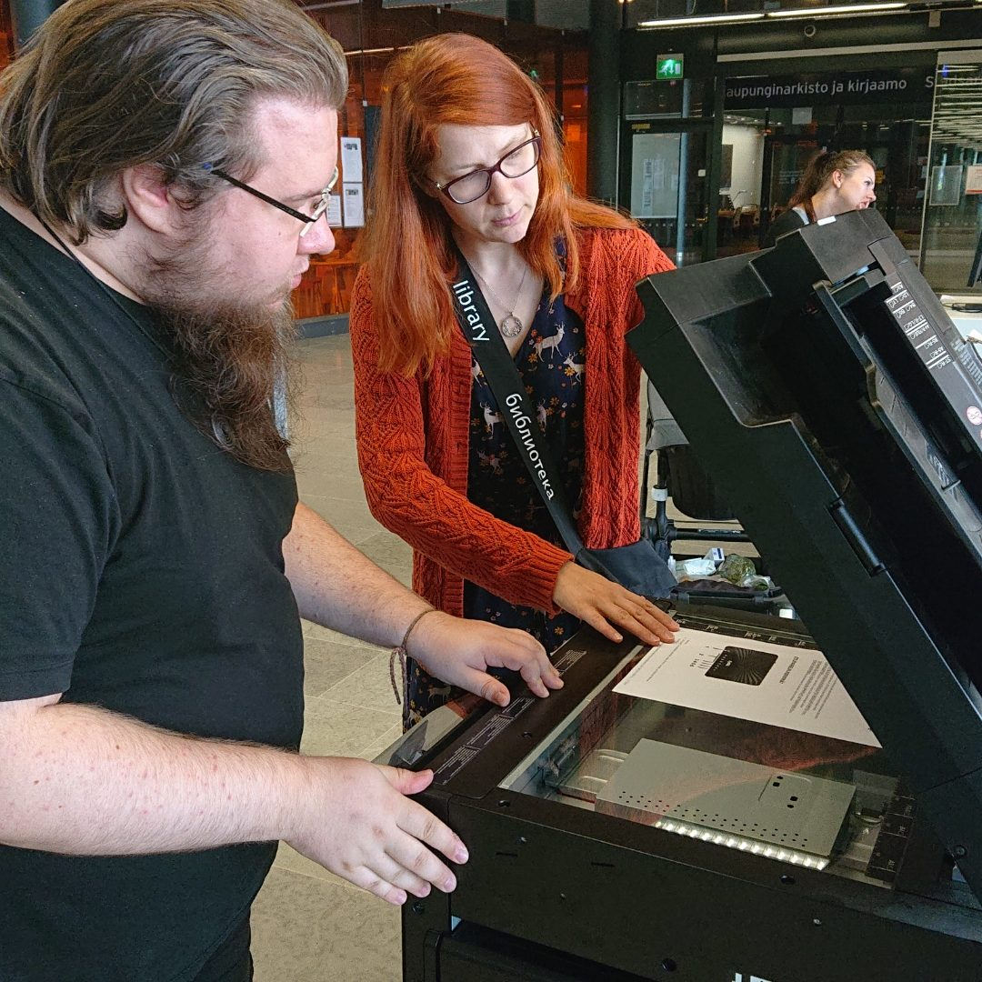 Henkilökunta opastaa asiakasta kopiokoneen käytössä