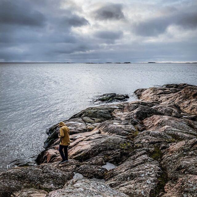 kivinen merenranta, ihminen sadetakissa rannalla.