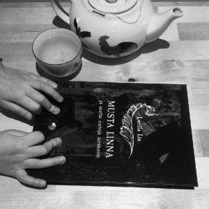 Lucilla Linin kirja Musta linna pöydällä teekannun ja kupin vieressä.